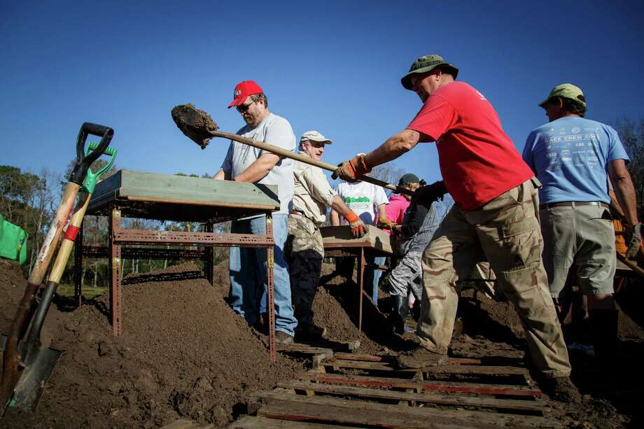 John Rich, right, scoops a load of dirt on a sorting table for 