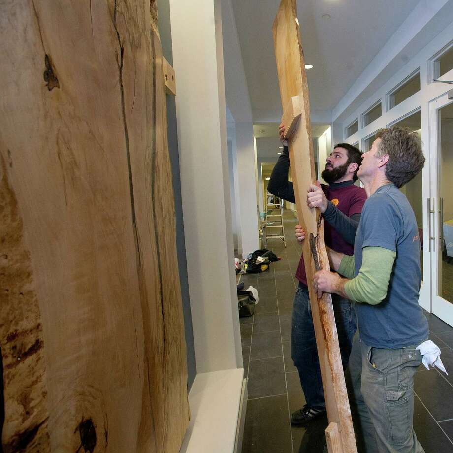 Ted Esselstyn, front, and Ben Konola, back, of City Bench put up wall art at 75 Tresser Blvd. in Stamford, Conn., on Friday, January 17, 2014. The wood slabs were made from the Copper Beech tree that once stood in front of the previous building. Photo: Lindsay Perry / Stamford Advocate