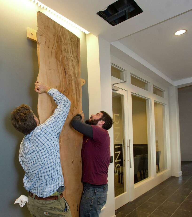Ted Esselstyn, left, and Ben Konola, right, of City Bench put up wall art at 75 Tresser Blvd. in Stamford, Conn., on Friday, January 17, 2014. The wood slabs were made from the Copper Beech tree that once stood in front of the previous building. Photo: Lindsay Perry / Stamford Advocate