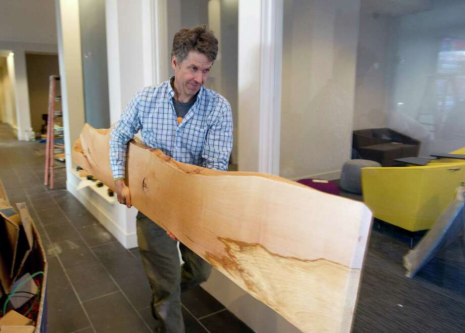Ted Esselstyn of City Bench puts up wall art at 75 Tresser Blvd. in Stamford, Conn., on Friday, January 17, 2014. The wood slabs were made from the Copper Beech tree that once stood in front of the previous building. Photo: Lindsay Perry / Stamford Advocate