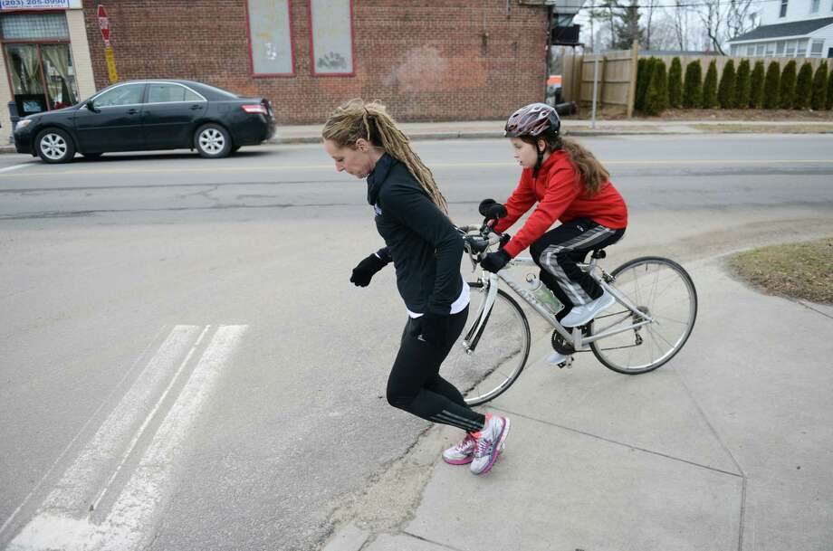 Heather Roles runs as her son, Elijah Crehan, 12, rides his bike near their home in Danbury, Conn. on Thursday, Jan. 17, 2014.  Roles is training for the Lake Placid Iron Man in July and bonds with her son through exercise. Photo: Tyler Sizemore / The News-Times