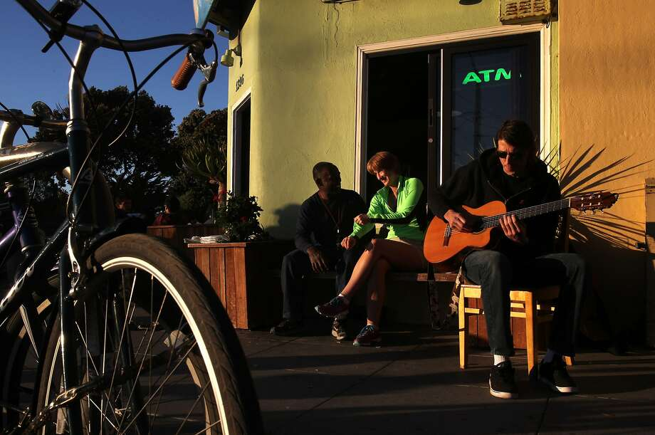 Mike Francois (left) and Sue Fry chat while Phil Stokes strums in the fading light outside Java Beach Cafe. Photo: Leah Millis, The Chronicle
