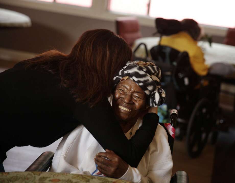 Cristina Flores (l to r),  Agesong chief operating and program officer, gives Velma Shaw a hug in a dining area at WoodPark on Monday, November 18, 2013  in Oakland, Calif. Photo: Lea Suzuki, The Chronicle