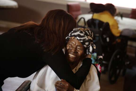 Cristina Flores (l to r),  Agesong chief operating and program officer, gives Velma Shaw a hug in a dining area at WoodPark on Monday, November 18, 2013  in Oakland, Calif.