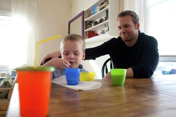 "Ryan McKinny helps his son get a snack at his north Houston home Monday, Jan. 13, 2014.  McKinny plays the title role in Houston Grand Opera's staging of Giuseppe Verdi's ""Rigoletto,"" McKinny, a California native, first came to Houston as a member of Houston Grand Opera's training program. After spending several years in Germany to continue his training and build his career, he moved back to Houston in 2012. Now he sings on both sides of the Atlantic.( Johnny Hanson / Houston Chronicle )"