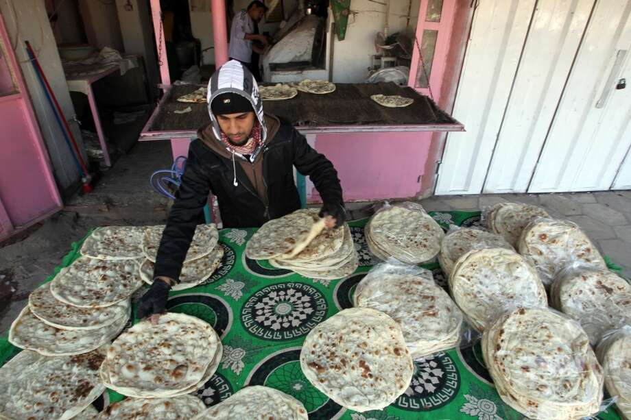 Iraq: Unleavened flat bread is stacked after cooling and made ready for sale at a bakery in central Baghdad. Photo: Ali Al-Saadi, AFP/Getty Images