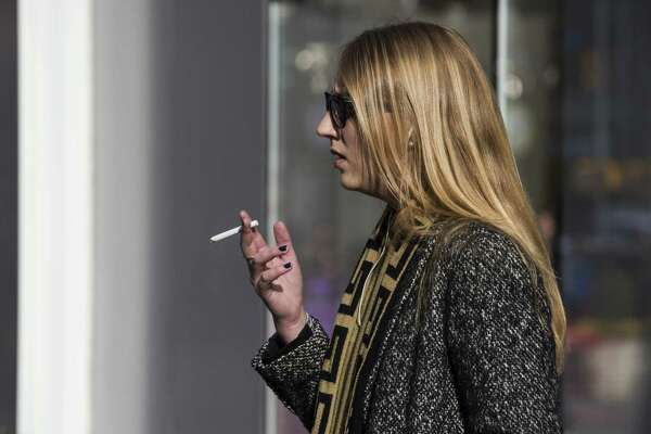 NEW YORK, NY - JANUARY 17:  A woman smokes a cigarette on January 17, 2014 in Times Square in New York City.  A new report from the Surgeon General shows the that list of negative side effects and diseases caused by cigarettes continues to grow, including diabetes, rheumatoid arthritis and erectile dysfunction.