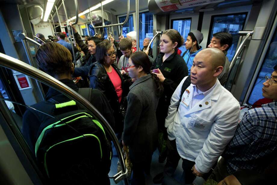 Samuel Kim, center left, a University of Texas student of medicine watches as more commuters make their way in to the southbound METRORail cart at the Memorial Hermann Hospital/Houston Zoo station, Wednesday, Jan. 15, 2014. ( Marie D. De Jesus / Houston Chronicle ) Photo: Marie D. De Jesus, Staff / Â 2014 Houston Chronicle