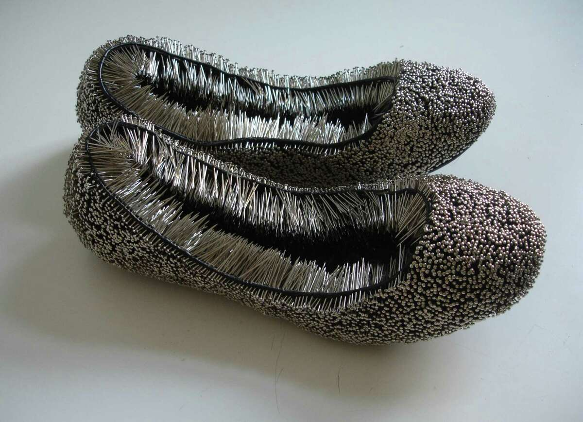"""Polish artist Erwina Ziomkowska's """"Untitled"""" shoes with pins (2013) is featured in """"Pins & Needles"""" through Feb. 20 at the Housatonic Museum of Art."""