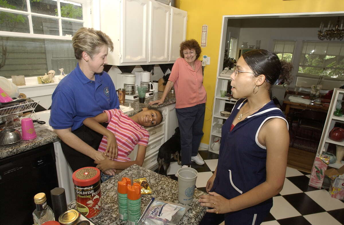 City Comptroller Anise Parker, far left, and her partner Kathy Hubbard were together for 12 1/2 years when they decided to adopt Marquitta, now 8. Marquitta's older sister Daniela, 13, joined the family a year ago this June. Planning for afternoon of shopping in Montrose home, Saturday, May 22, 2004. Chronicle/Ben DeSoto. HOUCHRON CAPTION (06/25/2004): City Controller Annise Parker, far left, and her partner Kathy Hubbard also faced an uphill battle when they adopted Marquitta, 9, and her older sister, Daniela, 13. Parker said the judge refused to let anyone in the court hear her case.