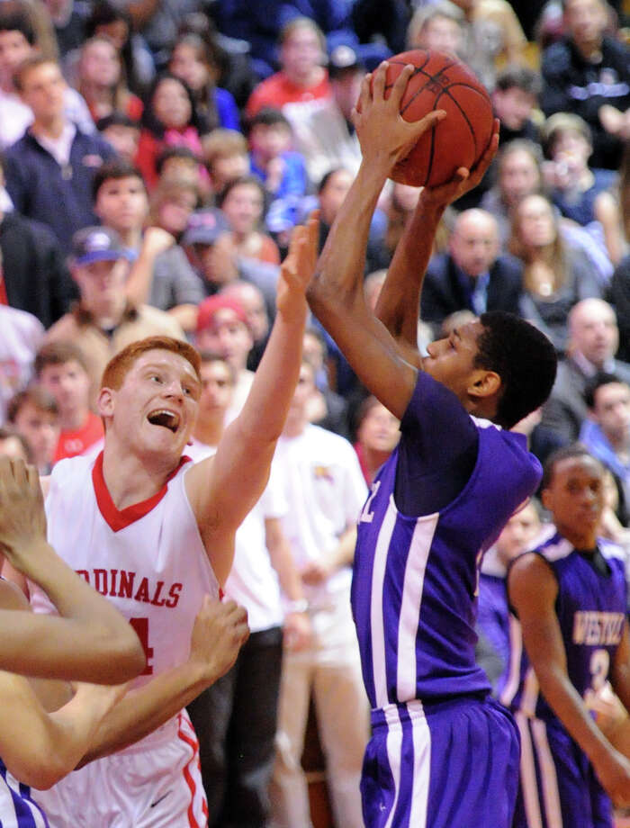 At left, Griffin Golden of Greenwich, shouts as he attempts to block a shot by Jeremiah Livingston, right, of Westhill, during the high school basketball game between Greenwich High School and Westhill High School at Greenwich, Friday night, Jan. 17, 2014. Photo: Bob Luckey / Greenwich Time
