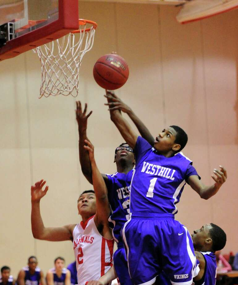 At right, Jeremiah Livingston (#1) of Westhill goes high to grab an offensive rebound against CJ Byrd (#2) of Greenwich, left, during the boys high school basketball game between Greenwich High School and Westhill High School at Greenwich, Friday night, Jan. 17, 2014. Photo: Bob Luckey / Greenwich Time