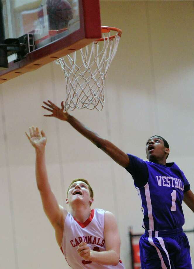 At left, Griffin Golden of Greenwich scores on a layup getting his shot past Jeremiah Livingston (#1) right, of Westhill, during the high school basketball game between Greenwich High School and Westhill High School at Greenwich, Friday night, Jan. 17, 2014. Photo: Bob Luckey / Greenwich Time