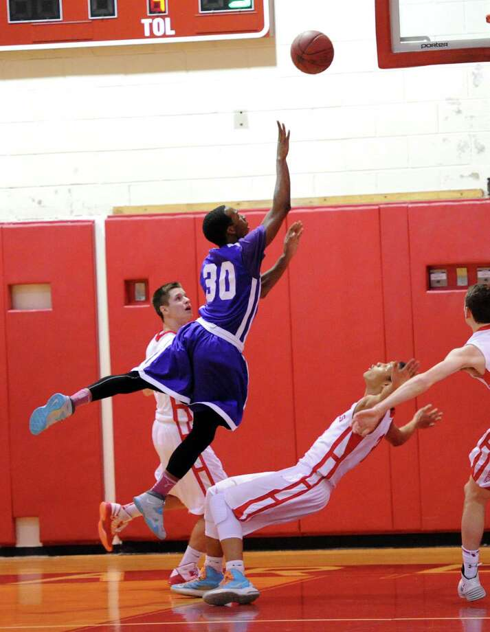 At left, Westhill's Jesse Brown (#30) shoots the ball but CJ Byrd, bottom, of Greenwich, is able to draw a charging foul during the boys high school basketball game between Greenwich High School and Westhill High School at Greenwich, Friday night, Jan. 17, 2014. Photo: Bob Luckey / Greenwich Time