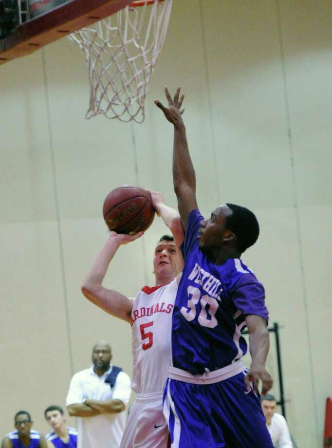 At right, Westhill's Jesse Brown (#30) blocks the layup attempt of Jon Palmer (#5) of Greenwich during the boys high school basketball game between Greenwich High School and Westhill High School at Greenwich, Friday night, Jan. 17, 2014. Photo: Bob Luckey / Greenwich Time