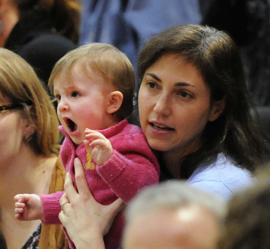 Although it looks like she is cheering, Avril Roth, 9 months old of Boston, is actually yawning while being held by her mother, Naomi Roth, before the start of the boys high school basketball game between Greenwich High School and Westhill High School at Greenwich, Friday night, Jan. 17, 2014. The pair were in town to visit relatives and were cheering Greenwich player Isaac Manton. Photo: Bob Luckey / Greenwich Time