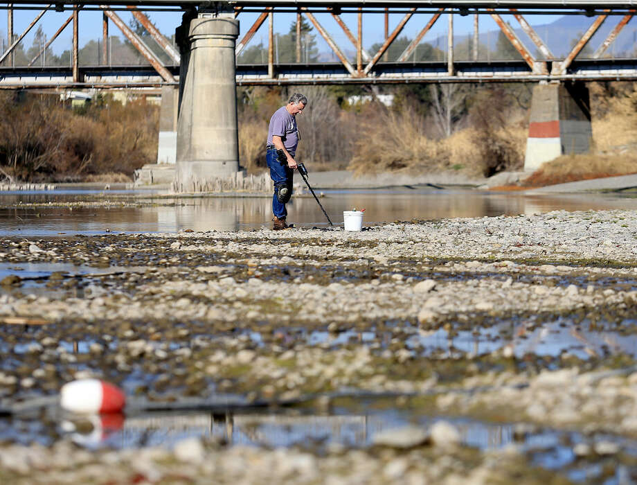 Hugh Beggs of Santa Rosa, Calif., searches for coins in the middle of the Russian River at Healdsburg Veterans Memorial Beach in Healdsburg, taking advantage of the low water level in the river. Photo: Kent Porter / Santa Rosa Press Democrat / Santa Rosa Press Democrat