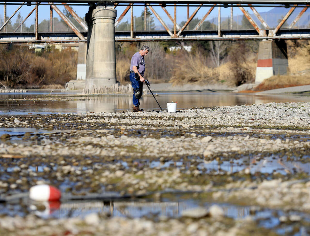 Hugh Beggs of Santa Rosa, Calif., searches for coins in the middle of the Russian River at Healdsburg Veterans Memorial Beach in Healdsburg, taking advantage of the low water level in the river.