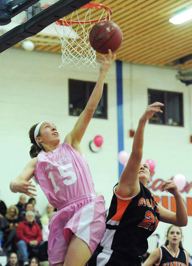 Danbury's Rebecca Gartner (15) makes a layup past Stamford's Kelsey Santagata (21) in Danbury's 40-27 win over Stamford in the girls high school basketball game at Danbury High School in Danbury, Conn. on Friday, Jan. 17, 2014. Photo: Tyler Sizemore / The News-Times