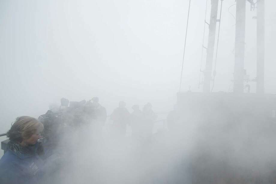 Fog and steam envelopes the top of the Space Needle before the 12th Man flag is raised by former Hawks Dave Wyman, Craig Terrill, Alex Bannister and Joe Tafoya on Friday, January 17, 2014 in preparation for the NFC Championship game between the Seahawks and 49ers. Photo: Joshua Trujillo, SEATTLEPI.COM / SEATTLEPI.COM