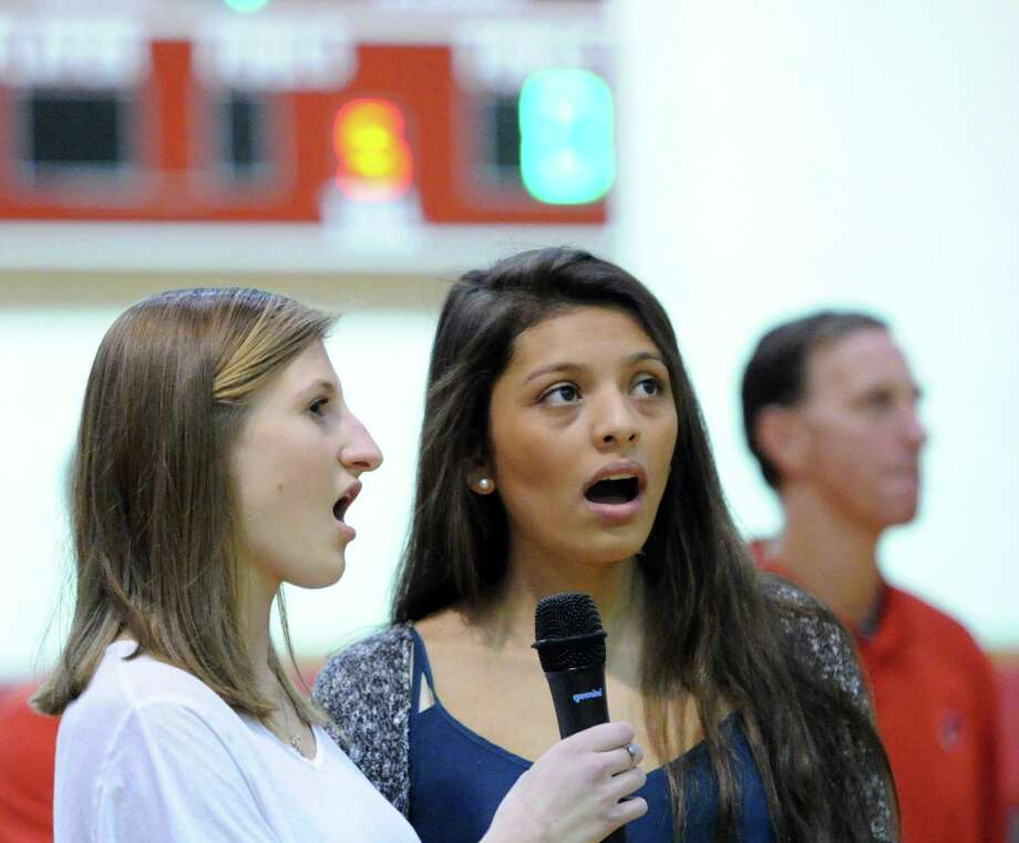 Greenwich High School students Claire Russack, 17, left, and Marcela Ruiz, also 17, sing the National Anthem at the start of the boys high school basketball game between Greenwich High School and Westhill High School at Greenwich, Friday night, Jan. 17, 2014. Photo: Bob Luckey / Greenwich Time