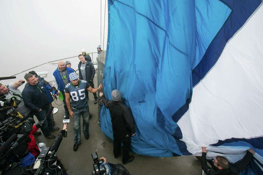 The 12th Man flag is raised on the Seattle Space Needle on by former Hawks Dave Wyman, Craig Terrill, Alex Bannister and Joe Tafoya on Friday, January 17, 2014 in preparation for the NFC Championship game between the Seahawks and 49ers. Photo: Joshua Trujillo, SEATTLEPI.COM / SEATTLEPI.COM