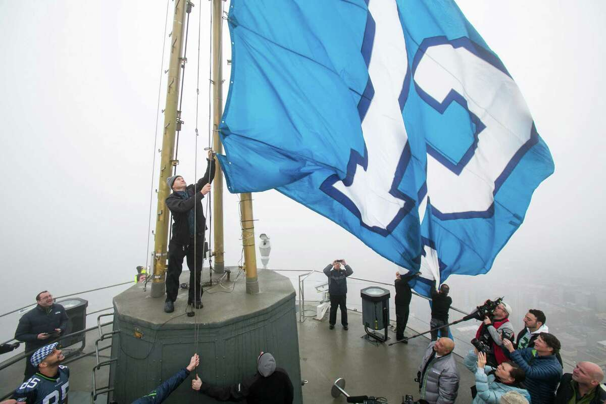 The 12th Man flag is raised on the Seattle Space Needle on by former Hawks Dave Wyman, Craig Terrill, Alex Bannister and Joe Tafoya on Friday, January 17, 2014 in preparation for the NFC Championship game between the Seahawks and 49ers.