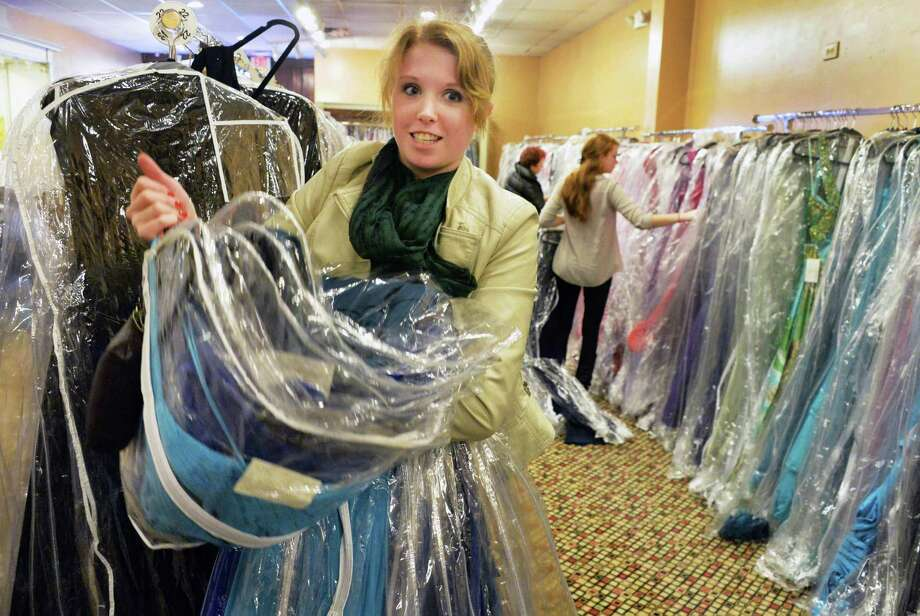 Ashley Watson of Nassau carries an armload of prom gowns to the fitting room during a $59 warehouse sale at Fancy Schmancy's old store Friday, Jan 17, 2014, on Western Ave. in Guilderland, N.Y.  (John Carl D'Annibale / Times Union) Photo: John Carl D'Annibale / 00025421A