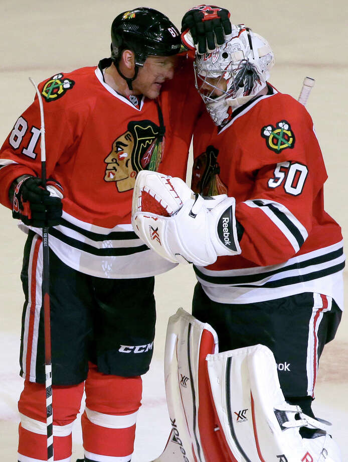 Chicago Blackhawks goalie Corey Crawford, right, celebrates with Marian Hossa after the Blackhawks defeated the Anaheim Ducks 4-2 in an NHL hockey game in Chicago, Friday, Jan. 17, 2014. (AP Photo/Nam Y. Huh) ORG XMIT: CXA113 Photo: Nam Y. Huh / AP
