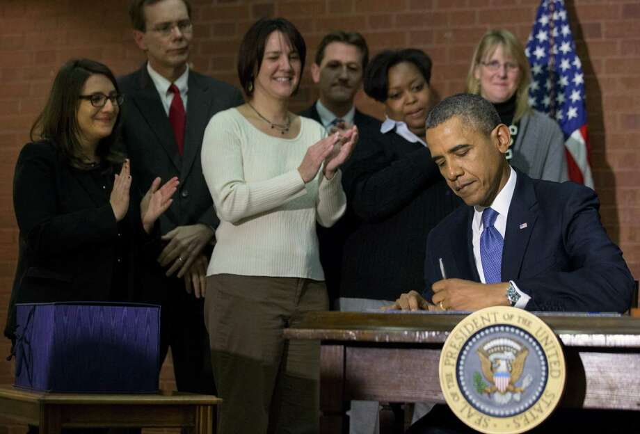 President Barack Obama signs the $1.1 trillion spending bill that funds the federal government through the end of September. The bill-signing was at Jackson Place, a conference center near the White House where many budget office employees work. Photo: Jacquelyn Martin / Associated Press / AP