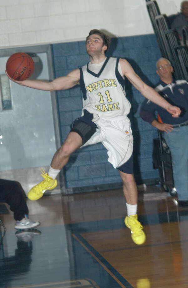 Jake Heaton, of Notre Dame-Fairfield, tries to keep the ball in bounds on Friday, Jan. 17 in an SWC boys basketball game against Newtown. The Lancers won 63-59. Photo: Andy Hutchison / Fairfield Citizen