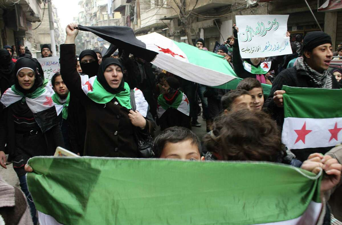 Syrian protesters in Aleppo shout during a demonstration calling for an end on the siege of Yarmouk Palestinian refugee camp in southern Damascus.