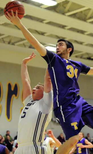 Troy's Connor Nicoll, right, goes to the hoop as CBA's  Nick Marini defends during their basketball