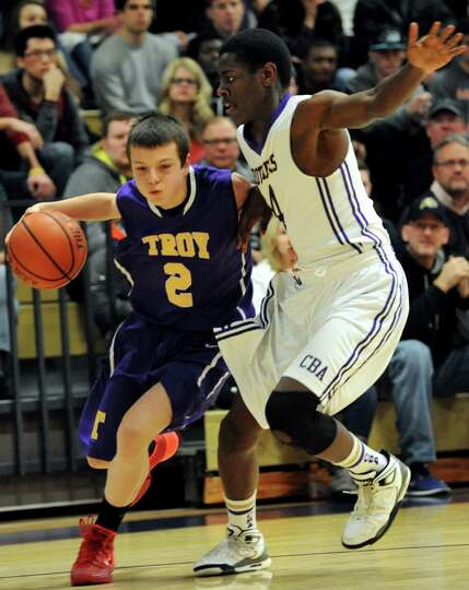 Troy's Ryan Carmello, left, controls the ball as CBA's Diamond Corker defends during their basketbal