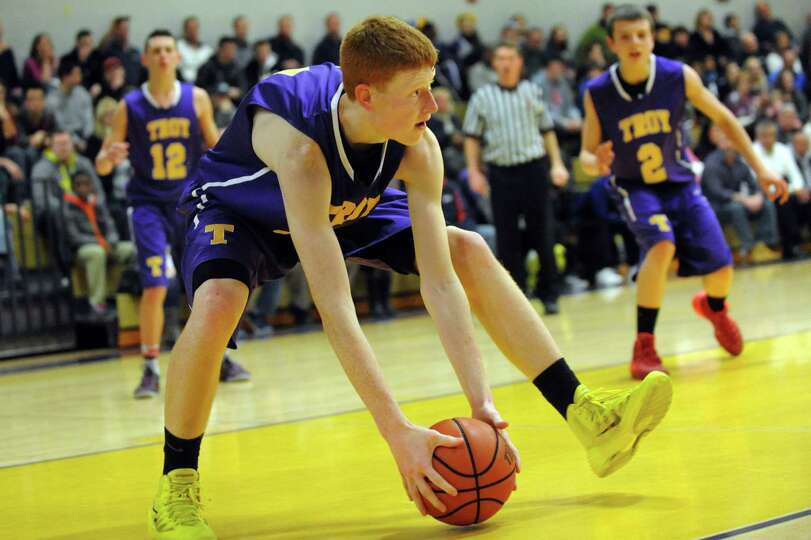 Troy's Jack McLaren, center, picks up a loose ball during their basketball game against CBA on Frida