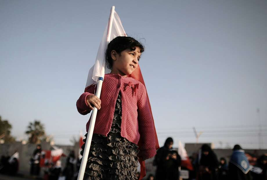 TOPSHOTS A young Bahraini girl holds a national flag during an anti-government rally in the village of Diraz, west of Manama, on January 17, 2014 .Bahrain's Crown Prince met opposition leaders on january 15, 2013 in a bid revive a national dialogue that was suspended last week. AFP PHOTO/MOHAMMED AL-SHAIKHMOHAMMED AL-SHAIKH/AFP/Getty Images Photo: Mohammed Al-shaikh, AFP/Getty Images