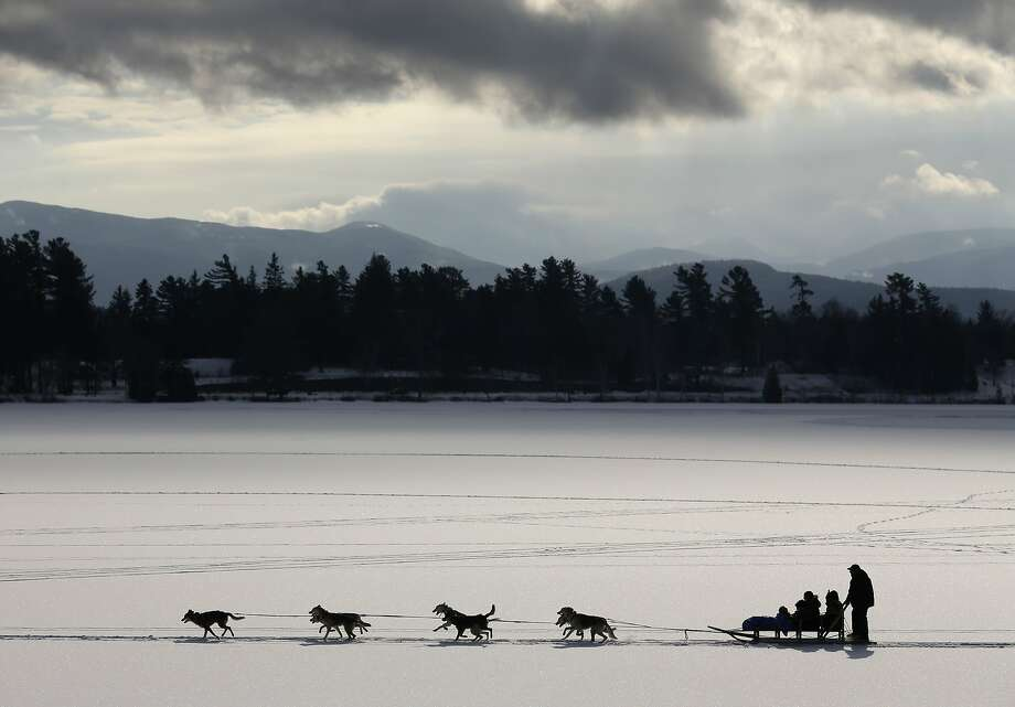 A dogsled team pulls passengers on a scenic ride across Mirror Lake on Friday, Jan. 17, 2014, in Lake Placid, N.Y. There is a 50 percent chance of snowfall in the Lake Placid area heading into the Martin Luther King Jr. holiday weekend. (AP Photo/Mike Groll) Photo: Mike Groll, Associated Press