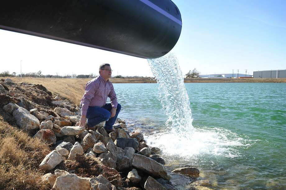Utilities Operations Manager Daniel Nix looks over the flow of the effluent water from the River Road Waster Water Treatment Plant Friday Jan. 17, 2014, in Wichita Falls, Texas as it pours into a permeate pond at the Cypress Water Treatment Plant after passing through microfiltration and reverse osmosis processes. The water then mixes with water from Lake Arrowhead and Lake Kickapoo and begins the traditional 7-step treatment process. The  process is preparing the plant for upcoming testing by  the Texas Commission on Environmental Quality and is not part of the city water supply at this time. If approved by the state, the project will provide approximately 5 million gallons of additional clean water per day to the city's system, which is almost half of current usage. (AP Photo/Wichita Falls Times Record News, Torin Halsey) Photo: Torin Halsey, Associated Press