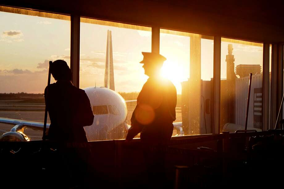 An airline pilot talks with a crew member between flights as the sun sets at the Charlotte Douglas International Airport in Charlotte, N.C., Friday Jan. 18, 2014. (AP Photo/J. David Ake) Photo: J. David Ake, Associated Press