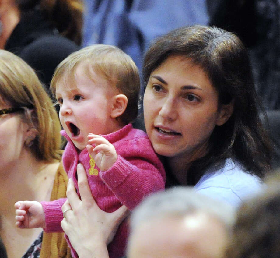 Although it looks like she is cheering, Avril Roth, 9 months old of Boston, is actually yawning while being held by her mother, Naomi Roth, before the start of the boys high school basketball game between Greenwich High School and Westhill High School at Greenwich, Friday night, Jan. 17, 2014. The pair were in town visiting and were cheering Greenwich player, Isaac Manton, they said. Greenwich defeated Westhill, 61-51, and remains undefeated. Photo: Bob Luckey / Greenwich Time