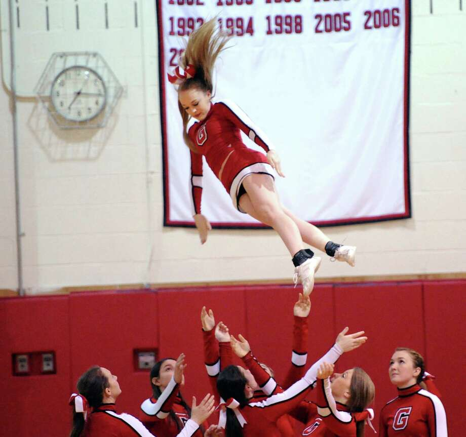 A Greenwich High School cheerleader flys through the air after being tossed by her teammates during a break in the action at the boys high school basketball game between Greenwich High School and Westhill High School at Greenwich, Friday night, Jan. 17, 2014. Greenwich defeated Westhill, 61-51, and remains undefeated. Photo: Bob Luckey / Greenwich Time