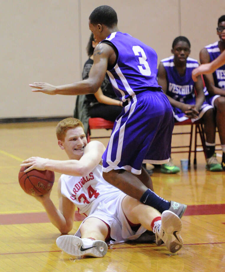 At left, Griffin Golden of Greenwich looks to pass from the floor after recovering a loose ball during the high school basketball game between Greenwich High School and Westhill High School at Greenwich, Friday night, Jan. 17, 2014. Defending on the play is C.J. Donaldson (#3) of Westhill. Greenwich defeated Westhill, 61-51, and remains undefeated. Photo: Bob Luckey / Greenwich Time