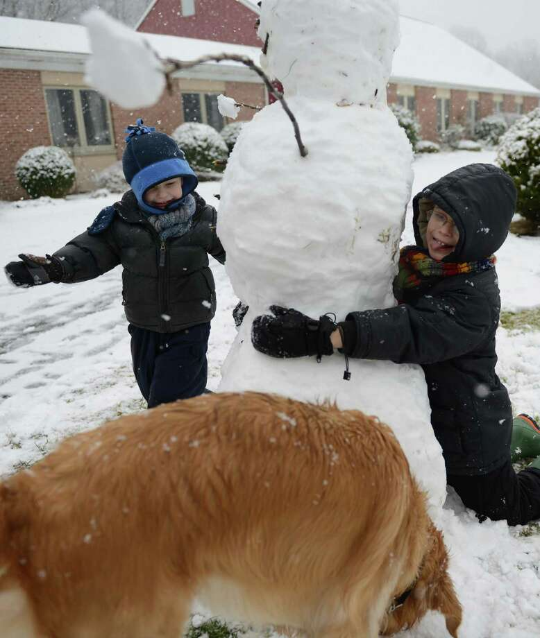 Isaiah Morris, left, 4, and his brother Elijah, 7, hug a snowman that they built in front of Christ the King Lutheran Church in Newtown, Conn. on Saturday, Jan. 18, 2014.  The area received a surprise snowstorm Saturday, with Danbury getting just one inch of snow but other areas getting up to three inches. Photo: Tyler Sizemore / The News-Times