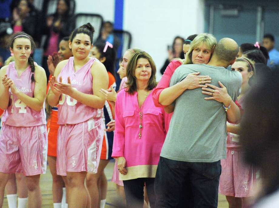 "Danbury head coach Jackie DiNardo hugs her brother, Paul DiNardo after the National Anthem before Danbury's game against Stamford on Friday, Jan. 17, 2014.  Fans packed the stands wearing pink for a ""Pink Out"" to raise cancer awareness and celebrate the memory of Jackie's husband, former assistant coach Bobby DiNardo, who died of cancer in 2009. Photo: Tyler Sizemore / The News-Times"