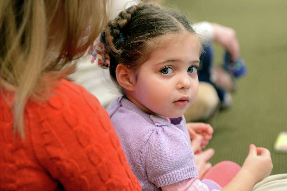 Three-year-old Simone Tsyrulnik, of Shelton, listens to a story during the Young Families Havurah at Congregation B'nai Israel in Bridgeport Saturday, Jan. 18, 2013.  The Shabbat morning community meets every Saturday morning at B'nai Israel for music, arts, fun, and more starting around 9:30 for bagels and then at 9:45 for Shabbat singing and service. All families with children 5 years and younger are welcome to attend. Photo: Autumn Driscoll / Connecticut Post