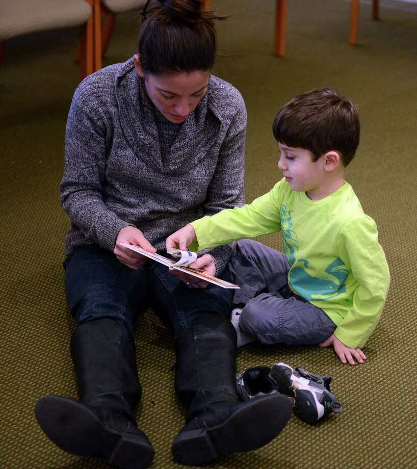Four-year-old Jonah Kerner reads a story with his mom Tara Kerner, of Fairfield, during the Young Families Havurah at Congregation B'nai Israel in Bridgeport Saturday, Jan. 18, 2013.  The Shabbat morning community meets every Saturday morning at B'nai Israel for music, arts, fun, and more starting around 9:30 for bagels and then at 9:45 for Shabbat singing and service. All families with children 5 years and younger are welcome to attend. Photo: Autumn Driscoll / Connecticut Post