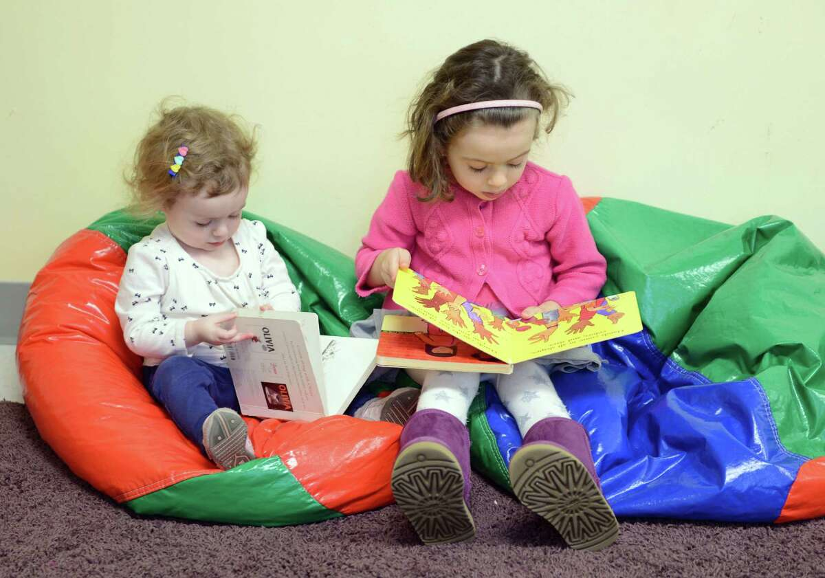 Sisters Emma, 17 months, and Paige Ringelheim, 3, read together during the Young Families Havurah at Congregation B'nai Israel in Bridgeport Saturday, Jan. 18, 2013. The Shabbat morning community meets every Saturday morning at B'nai Israel for music, arts, fun, and more starting around 9:30 for bagels and then at 9:45 for Shabbat singing and service. All families with children 5 years and younger are welcome to attend.