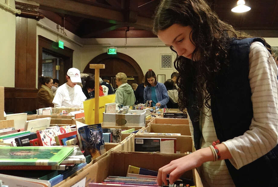 Caroline Dayton of Fairfield flips through selections of young adult books at Pequot Library's Mid-Winter Book Sale on Saturday. Photo: Mike Lauterborn / Fairfield Citizen contributed