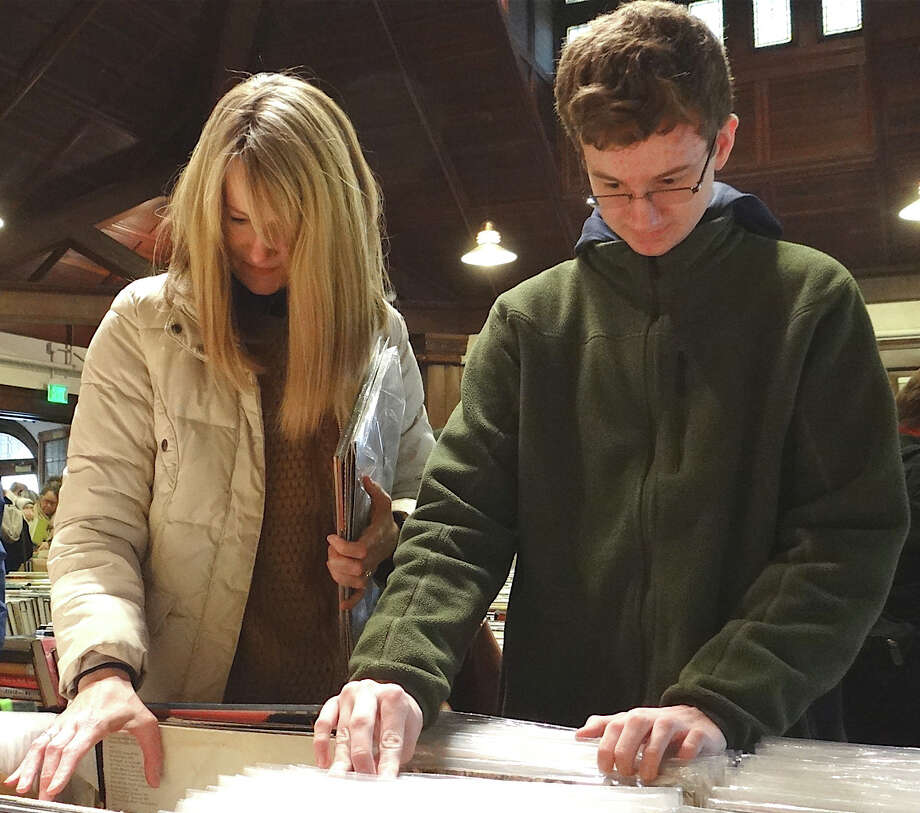 Elaine Anderson and son Ben review vinyl record albums at the Pequot Library on Saturday. Photo: Mike Lauterborn / Fairfield Citizen contributed