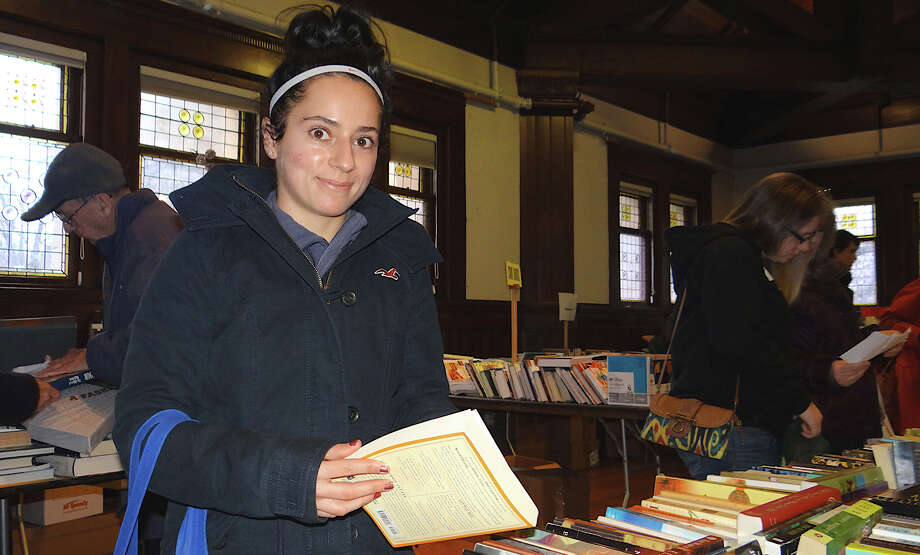 Geraldine Pires of Fairfield looks at fiction on sale at the Pequot Library's Mid-Winter Book Sale. Photo: Mike Lauterborn / Fairfield Citizen contributed